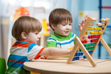 indoors: preschooler children boys play with counter toy Stock Photo