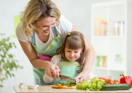 a little dinner: Cute mother teaches child daughter to cook Stock Photo