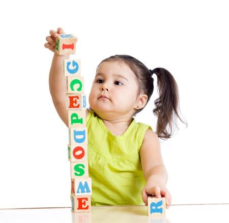乳幼児: 白い背景の上のブロックのおもちゃで遊ぶ子供の女の子