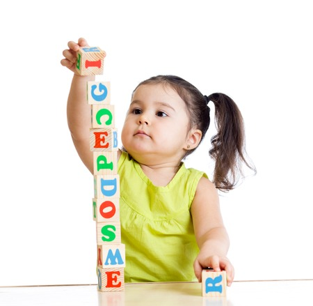 happy baby: child girl playing with block toys on white background