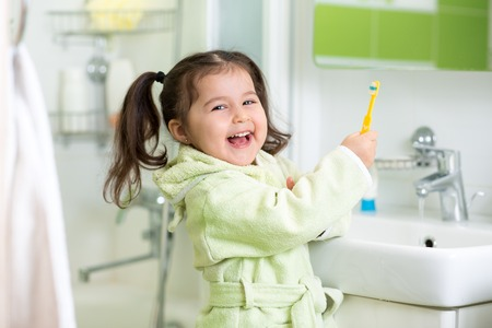 Kid little girl brushing teeth in bath