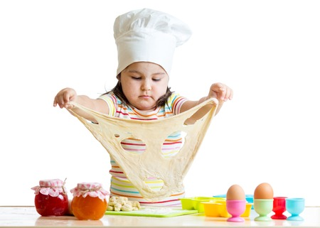 little dough: Little child girl in cap of the cook playing with dough