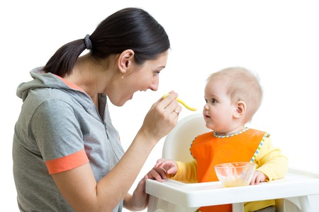 highchair: mother feeding baby girl with spoon isolated on white
