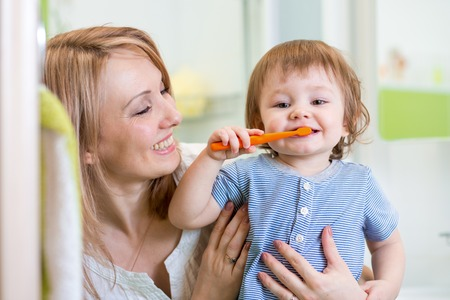 human tooth: smiling mother and kid son brushing teeth in bathroom