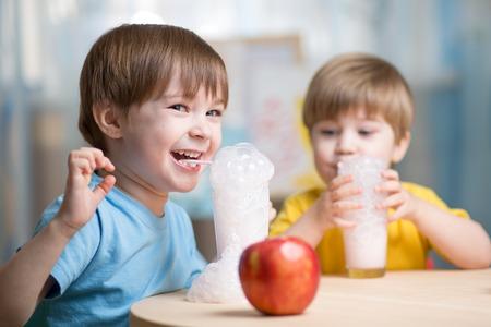 frutas divertidas: los niños que beben leche y que se divierten en el hogar