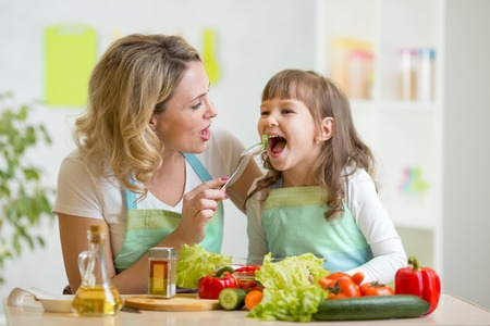 child couple: mom feeding child daughter vegetables in kitchen