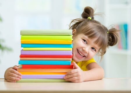 Playful kid girl with a stack of books at home