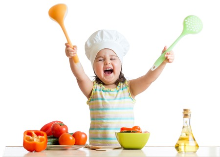 cheerful little girl in cook hat with skimmer and ladle photo