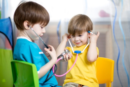 funny doctor: kid boy weared as doctor role playing with his younger brother