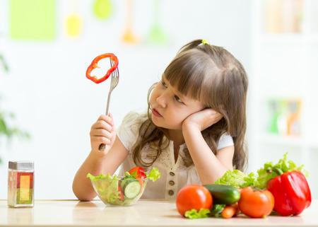 witaminy: Słodkie dziecko dziewczyna nie chce jeść zdrowe jedzenie w kuchni