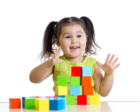 toddler child girl playing wooden toy blocks isolated photo