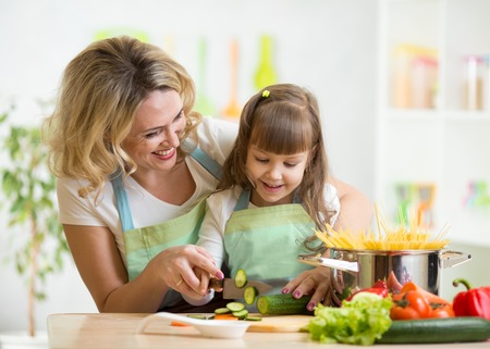 Cute mother teaches kid child cooking on kitchen