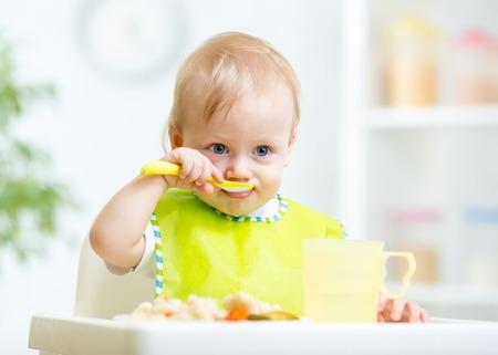 aliments droles: Happy Baby enfant assis dans un fauteuil avec une cuill�re Banque d'images