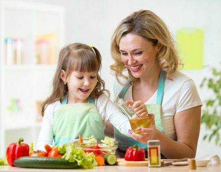a little dinner: mother and kid girl preparing healthy food at home Stock Photo