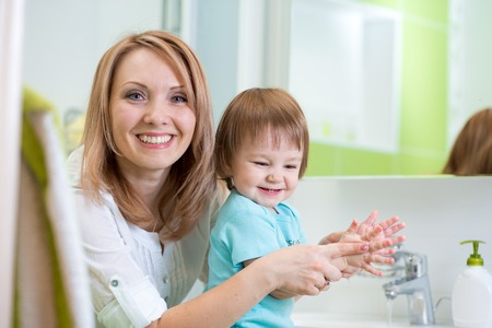 hand wash: Happy mother and child washing hands with soap together in bathroom Stock Photo