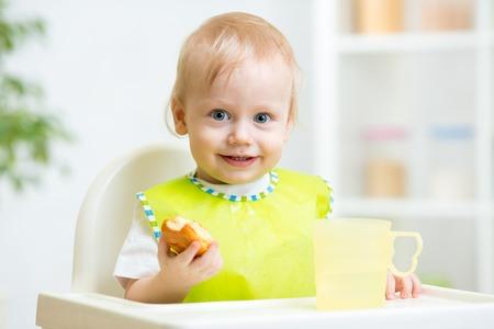 highchair: happy child boy eating food in highchair