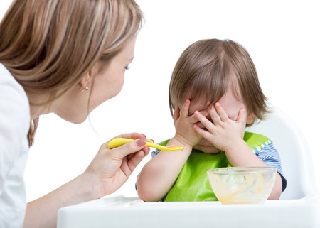 Little boy refuses to eat closing face by hands, isolated on white