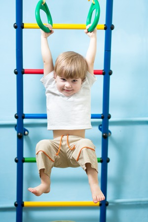 gymnastics equipment: cute child boy hanging on gymnastic rings at home
