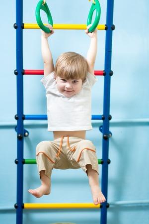 gymnastique: mignon enfant gar�on suspendu � anneaux de gymnastique � la maison Banque d'images