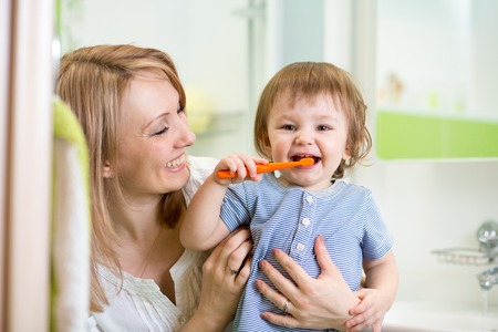 dentists: mother teaching son child teeth brushing in bathroom