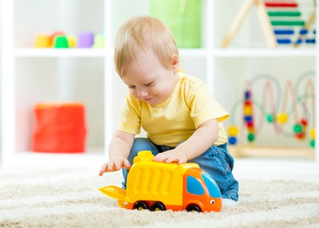 nursery room: kid boy toddler playing with toy car indoors Stock Photo