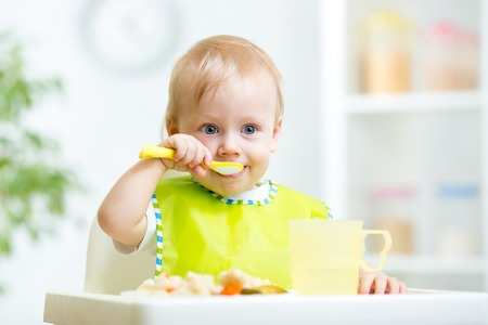 preschool kids: kid eating healthy food with a spoon at kitchen