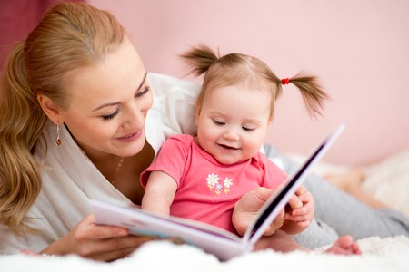 happy mother read a book to baby girl at home Stock Photo