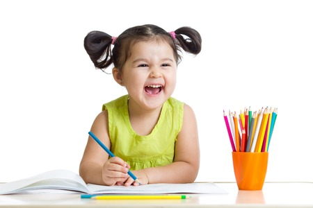 Adorable child drawing with colorful crayons and smiling, isolated on white Foto de archivo