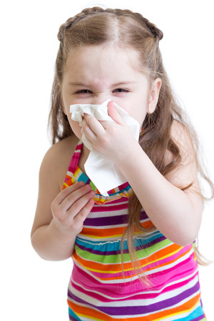 sick child wiping or cleaning nose with tissue isolated on white Stock Photo
