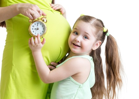 child looking at alarm clock and pregnant woman belly photo