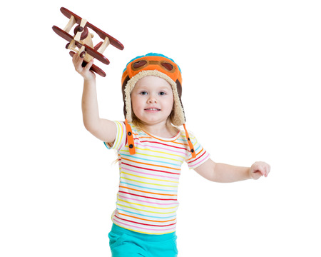 pilot helmet: happy kid girl dressed pilot and playing with wooden airplane toy