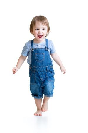 Gelukkig kind kleine jongen loopt geïsoleerd over een witte