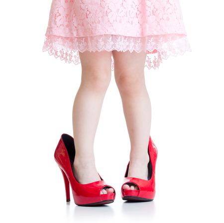 Kleines Mädchen, das ihrer Mutter Schuhe auf dem Boden - isoliert Standard-Bild