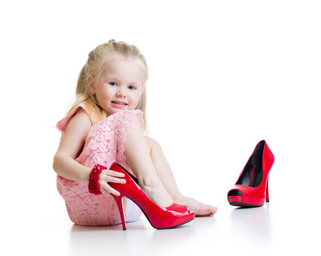 dress shoe: Little girl trying on mummys shoes isolated
