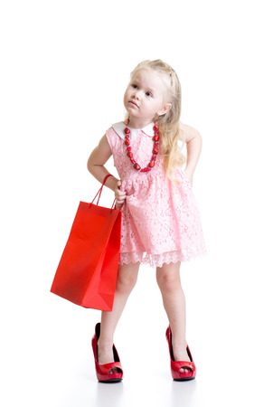 Funny little girl trying on her mother accessories and shoes isolated on white background photo