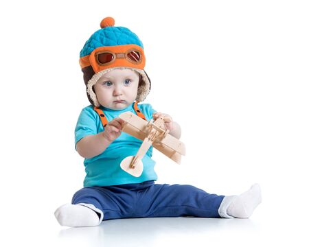 pilot helmet: baby boy dressed pilot helmet with wooden airplane toy