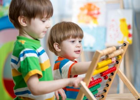 niñez: hermanos Niños felices jugar con el juguete ábaco en la sala de los niños