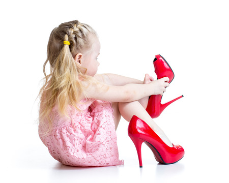 put: Kid girl trying red mummy shoes on.  Isolated on white