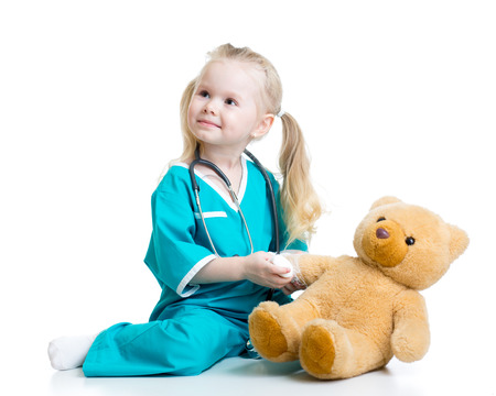 medical dressing: kid girl playing doctor with toy isolated Stock Photo