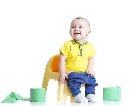 smiling child sitting on chamber pot with toilet paper rolls photo