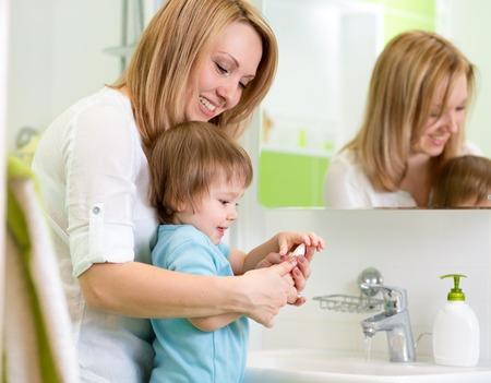mère enseigne fils enfant se laver les mains avec du savon dans la salle
