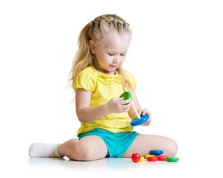 girl with rings: cute kid playing with color pyramid toy