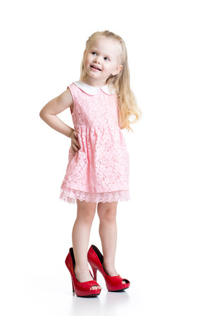 Cute toddler girl wearing big shoes isolated Stock Photo