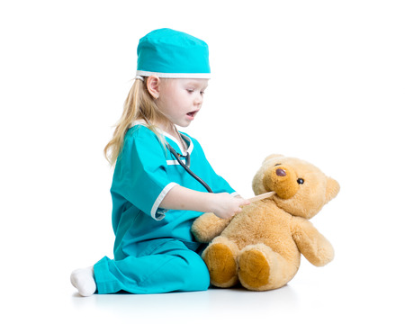 kid at doctor: Adorable child dressed as doctor playing with toy over white