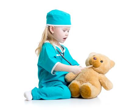 niños enfermos: Niño adorable vestido como médico jugar con el juguete sobre blanco