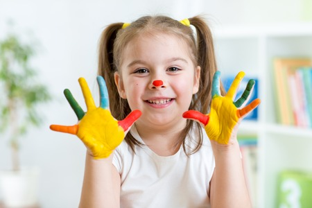 kindergarten education: Five year old girl with hands painted in colorful paints over playroom background