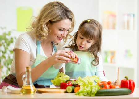 a little dinner: mother with kid make vegetable salad at kitchen