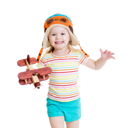 happy child girl dressed pilot and playing with wooden airplane toy photo