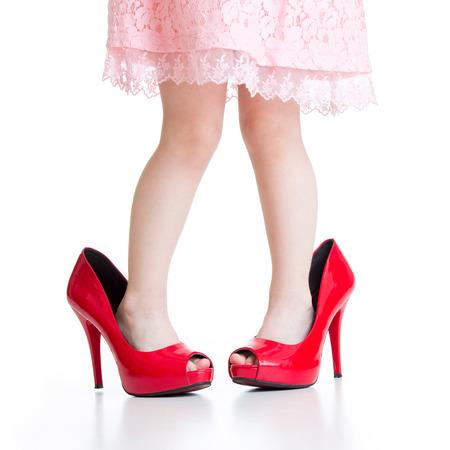 piernas con tacones: Pequeño niño que juega con los zapatos rojos de la mama aislado Foto de archivo