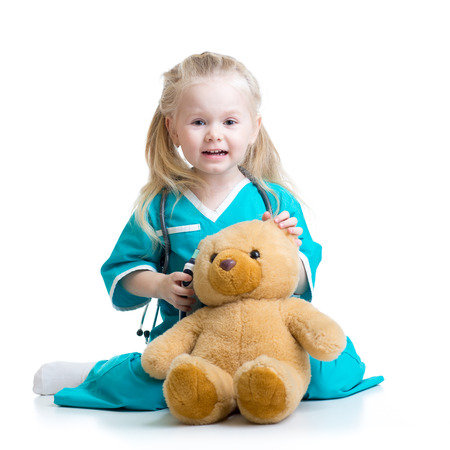 plush toy: kid girl playing doctor with plush toy isolated